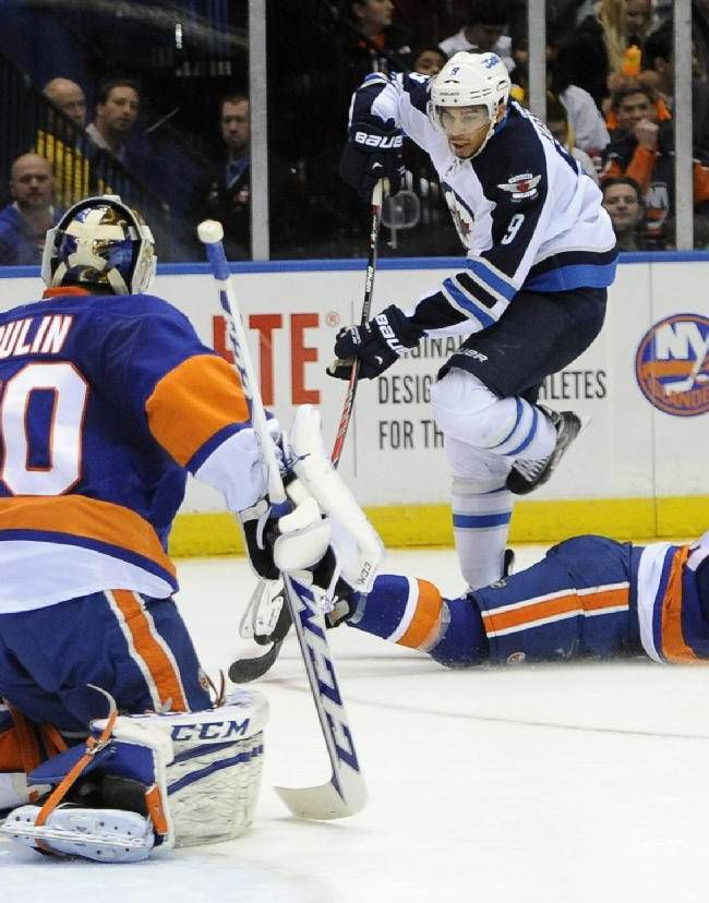 Winnipeg Jets' Evander Kane (9) skips over a fallen New York Islanders' Matt Donovan (46) to take a shot on goal at goalie Kevin Poulin (60) in the first period of an NHL hockey game on Wednesday, Nov. 27, 2013, in Uniondale, N.Y