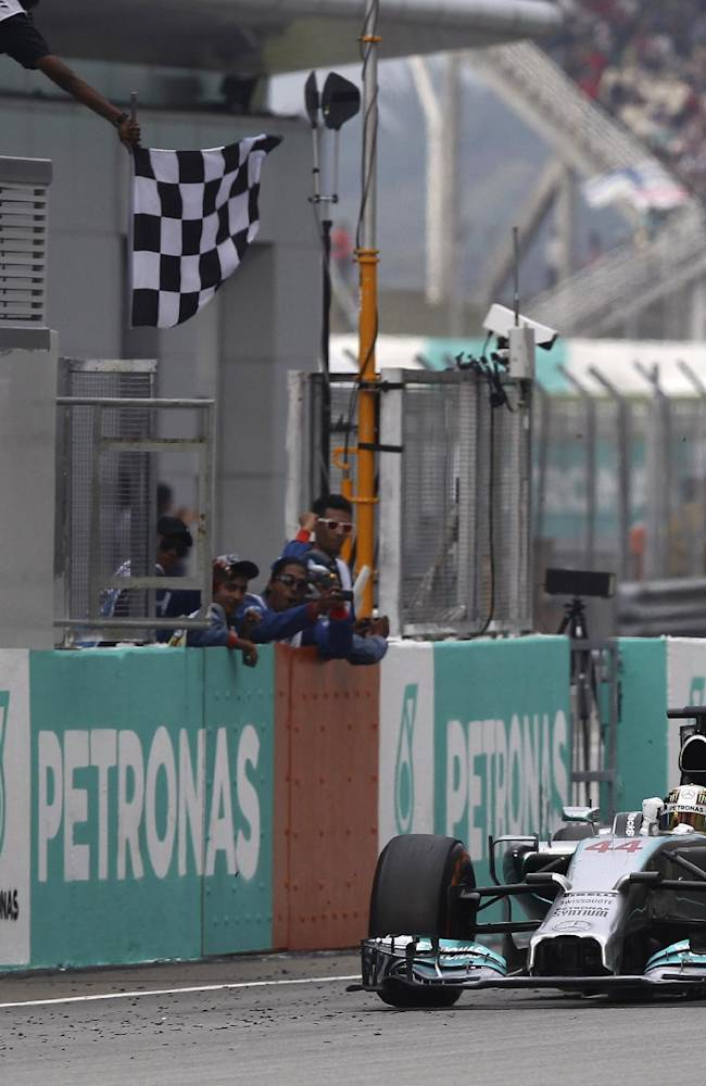 Mercedes driver Lewis Hamilton of Britain celebrates while crossing the finish line to win the Malaysian Formula One Grand Prix at Sepang International Circuit in Sepang, Malaysia, Sunday, March 30, 2014