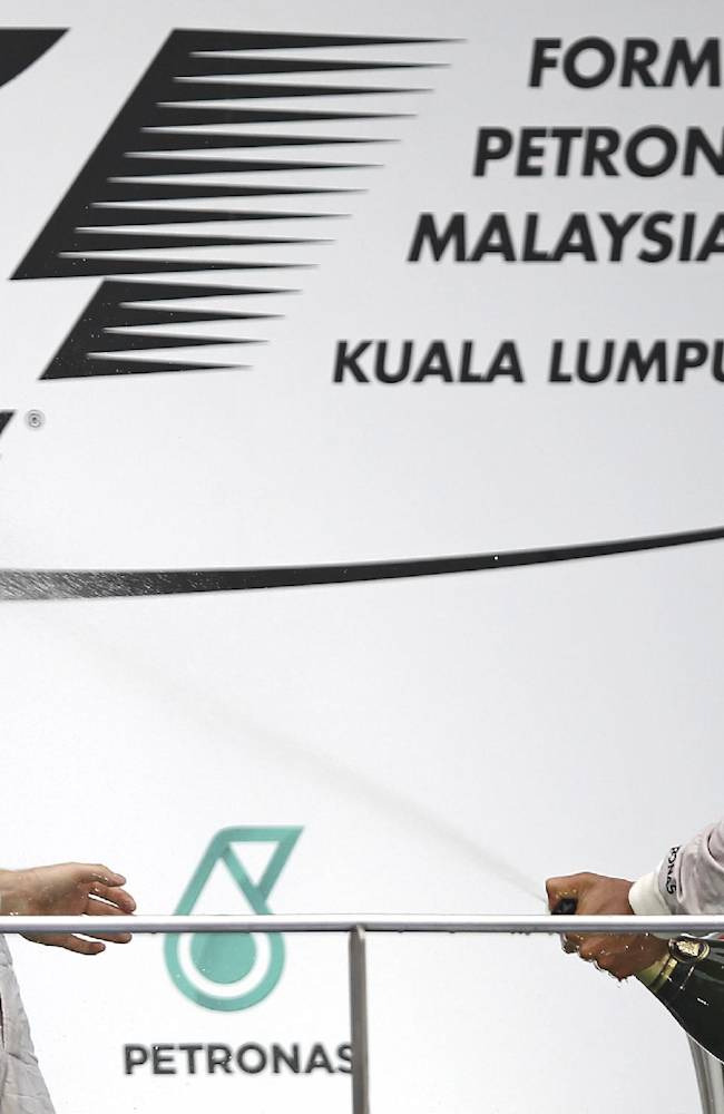 Mercedes driver Lewis Hamilton, right, of Britain sprays champagne to his teammate Nico Rosberg during the prize presentation on the podium after the Malaysian Formula One Grand Prix at Sepang International Circuit in Sepang, Malaysia, Sunday, March 30, 2014. Hamilton won the race while Rosberg finished in second