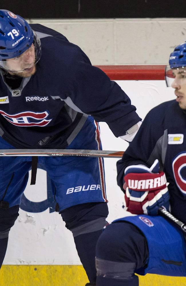 Montreal Canadiens defensemen Andrei Markov, left, and Alexei Emelin chat during NHL hockey practice Wednesday, April 30, 2014, in Brossard, Quebec. The Canadiens face the Boston Bruins in Game 1 in the second round of the Stanley Cup playoffs Thursday in Boston