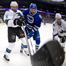 San Jose Sharks' Jason Demers, left, and Vancouver Canucks' Brad Richardson vie for the puck as Sharks' Joe Pavelski, right, watches during the first period of an NHL hockey game, Thursday, Nov. 14, 2013 in Vancouver, British Columbia The Associated Press
