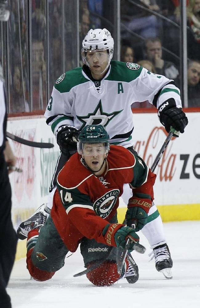 Minnesota Wild right wing Justin Fontaine (14) falls as he passes the puck in front of Dallas Stars defenseman Stephane Robidas (3) during the second period of an NHL hockey game in St. Paul, Minn., Saturday, Oct. 12, 2013