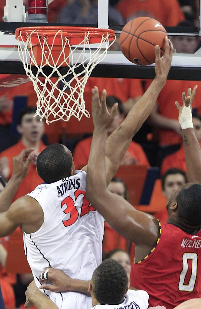 Virginia forward Darion Atkins (32) grabs a rebound in front of Maryland forward Charles Mitchell (0) during the second half of an NCAA college basketball game in Charlottesville, Va., Monday, Feb. 10, 2014. Virginia won the game 61-53