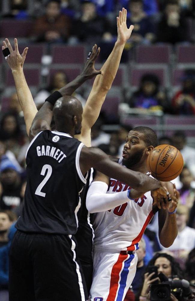 Detroit Pistons center Greg Monroe (10) has the ball knocked away by Brooklyn Nets forwards Kevin Garnett (2) and Mirza Teletovic during the first half of an NBA basketball game on Friday, Dec. 13, 2013, in Auburn Hills, Mich