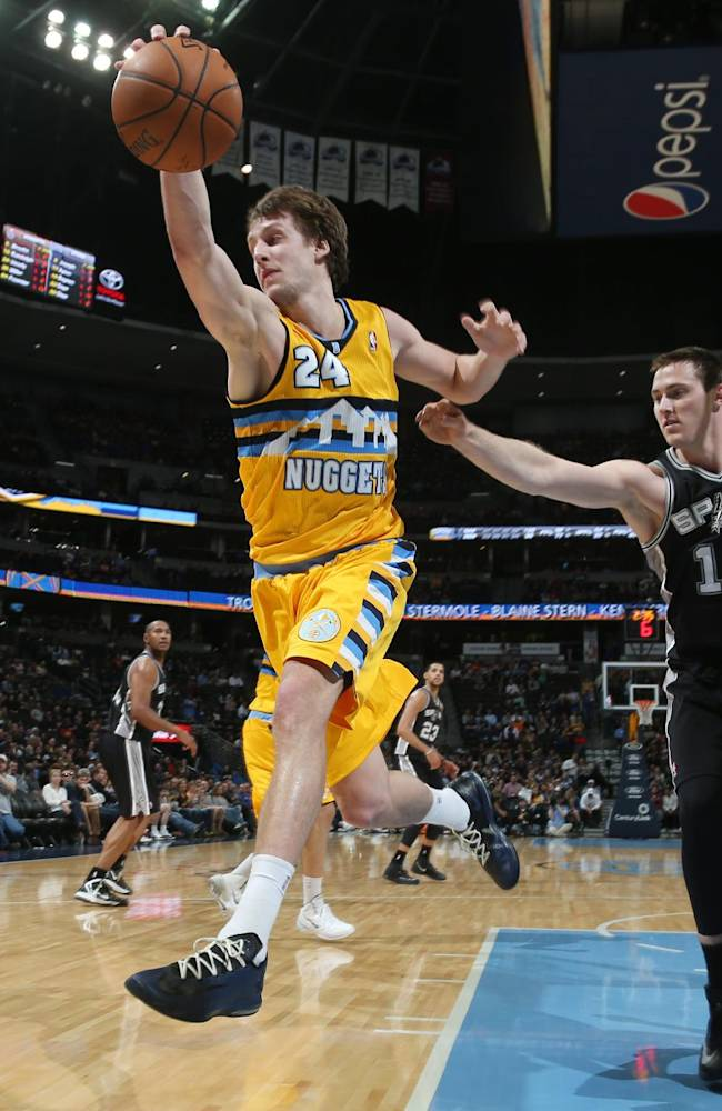 Denver Nuggets forward Jan Vesely, front, of the Czech Republic, reaches to pull in a loose ball as San Antonio Spurs forward Aron Baynes covers in the fourth quarter of the Spurs' 133-102 victory in an NBA basketball game in Denver, Friday, March 28, 2014