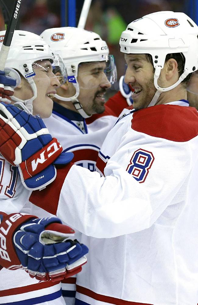 Montreal Canadiens center Tomas Plekanec, second from left, of the Czech Republic,  celebrates with teammates, including Brendan Gallagher, left, Brandon Prust, second from right, and Andrei Markov, right, after scoring against the Tampa Bay Lightning during the first period of Game 1 of a first-round NHL hockey playoff series on Wednesday, April 16, 2014, in Tampa, Fla