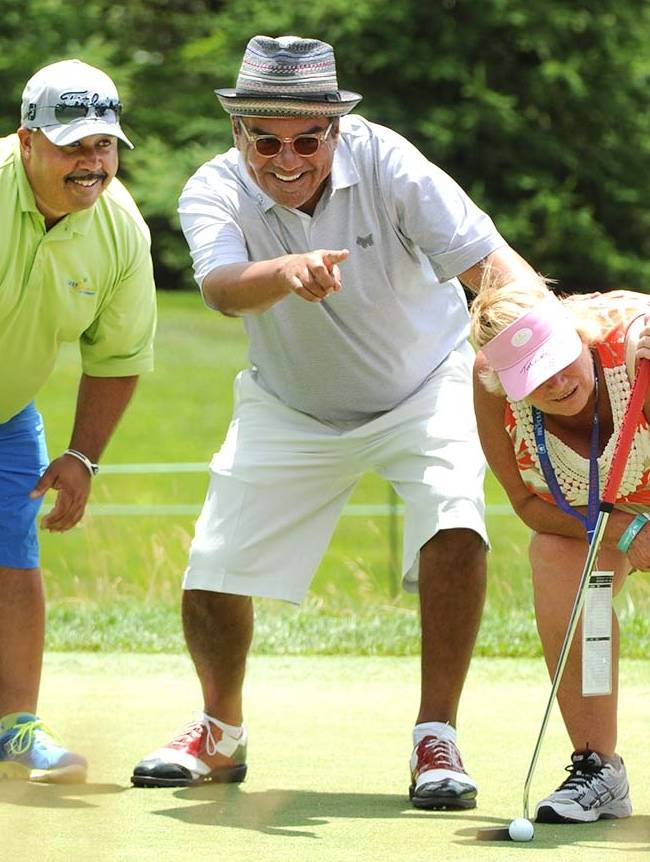 Comedian George Lopez, center, and his caddie Michael Collins, left, help Bev Taylor line up a putt on the third hole during The Greenbrier Classic golf tournament in White Sulphur Springs, W.V., Wednesday, July 2, 2014. Lopez pulled Taylor from the crowd to let her hit his putt