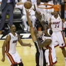 San Antonio Spurs power forward Tim Duncan (21) and Miami Heat small forward LeBron James (6) collide under the basket during the first half of Game 2 of the NBA Finals basketball game, Sunday, June 9, 2013 in Miami. (AP Photo/Wilfredo Lee)