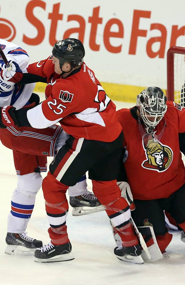 Ottawa Senators' Chris Neil (25) checks New York Rangers' Dominic Moore (28) as Senators goaltender Robin Lehner covers the puck during first period NHL hockey action in Ottawa, Ontario, Tuesday March 18, 2014