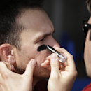 An Arizona Diamondbacks trainer, right, applies eye black to Arizona Diamondbacks catcher Miguel Montero, left, before the Diamonbacks play the Kansas City Royals in an exhibition spring training baseball game Wednesday, March 5, 2014, in Scottsdale, Ariz
