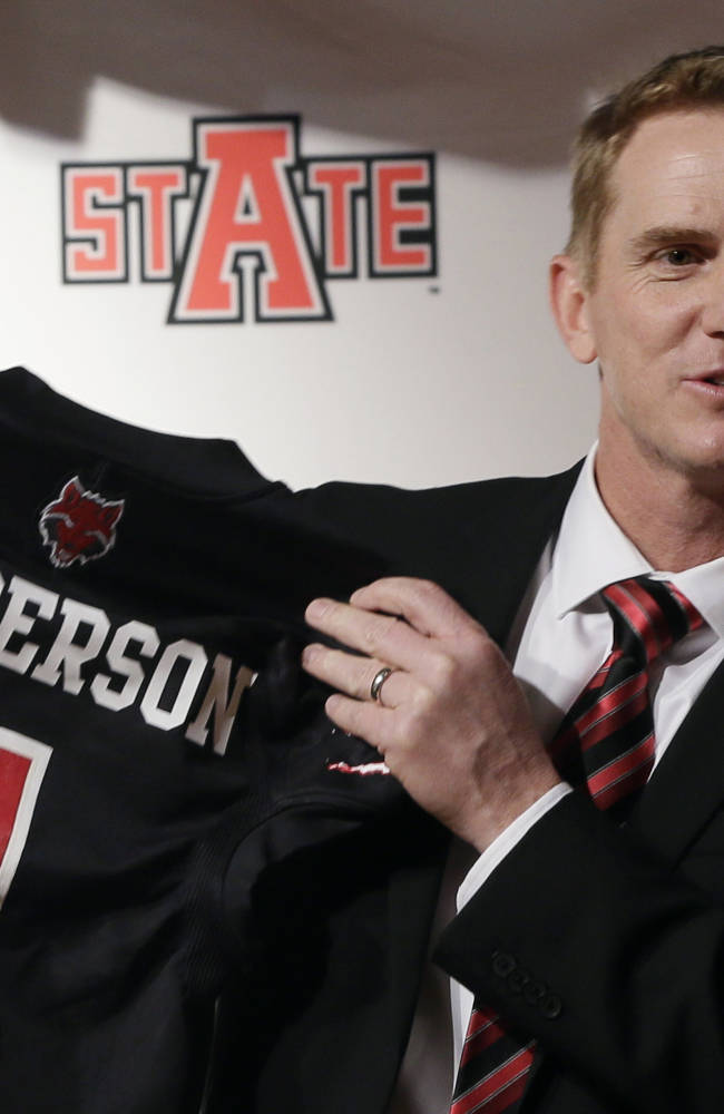 Former North Carolina offensive coordinator Blake Anderson holds an Arkansas State jersey at the school in Jonesboro, Ark., Thursday, Dec. 19, 2013. Anderson was named head football coach at Arkansas State, Thursday