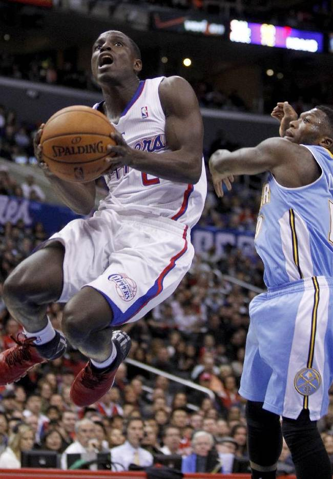 Los Angeles Clippers guard Darren Collison, left, gets past Denver Nuggets guard Nate Robinson on the way to the basket during the first half of an NBA basketball game in Los Angeles on Saturday, Dec. 21, 2013