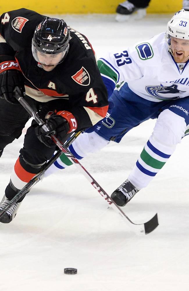 Ottawa Senators' Chris Phillips, left, fights to keep the puck from Vancouver Canucks' Henrik Sedin during first-period NHL hockey game action in Ottawa, Ontario, Thursday, Nov. 28, 2013