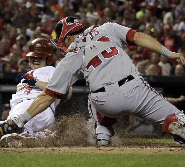 St. Louis Cardinals' Yadier Molina, left, is tagged out at the plate by Washington Nationals catcher Wilson Ramos during the fourth inning of a baseball game Tuesday, Sept. 24, 2013, in St. Louis