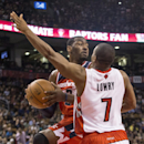 Washington Wizards' John Wall, left, looks to pass around Toronto Raptors' Kyle Lowry during the first half of an NBA basketball game in Toronto on Friday, Nov. 22, 2013 The Associated Press
