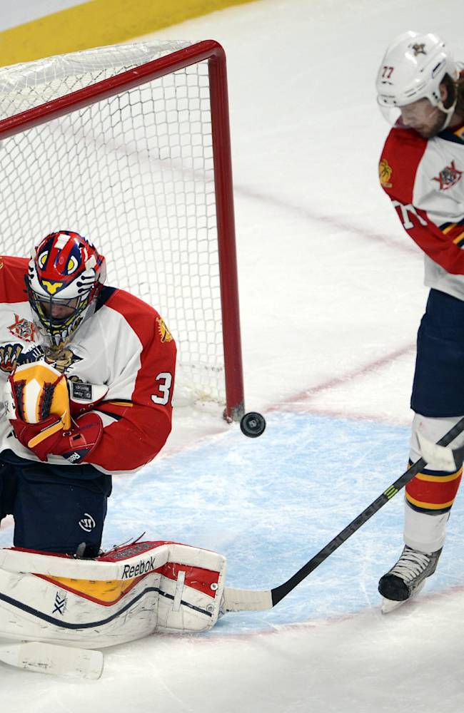 Florida Panthers goalie Scott Clemmensen (30) makes a save as Montreal Canadiens left wing Michael Bournival (49) and Panthers defenseman Tom Gilbert (77) look for the rebound during first-period NHL hockey action on Sunday, Dec. 15, 2013, in Montreal