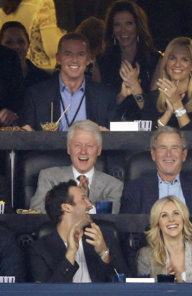 From center left, Dallas Cowboys owner Jerry Jones, former presidents Bill Clinton and George W. Bush and former first lady Laura Bush as well as Cowboys head coach Jason Garrett, second from top left, watch action between Connecticut and Kentucky during the first half of the NCAA Final Four tournament college basketball championship game Monday, April 7, 2014, in Arlington, Texas