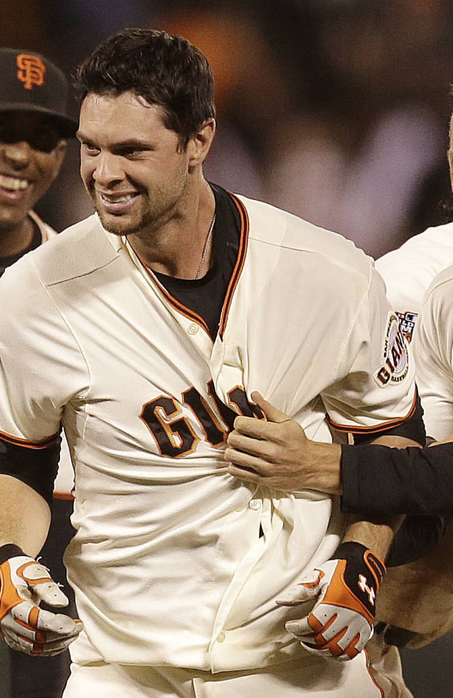 San Francisco Giants' Brandon Belt, center, celebrates with Joaquin Arias, left, and Hunter Pence after Belt hit the game winning hit in the tenth inning of a baseball game against the Colorado Rockies Monday, Sept. 9, 2013, in San Francisco