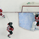 Detroit Red Wings left wing Johan Franzen, top left, of Sweden, stands by the net as the puck bounces off the net after his a goal on New Jersey Devils goalie Cory Schneider, right, as center Adam Henrique is near during the third period of an NHL hockey