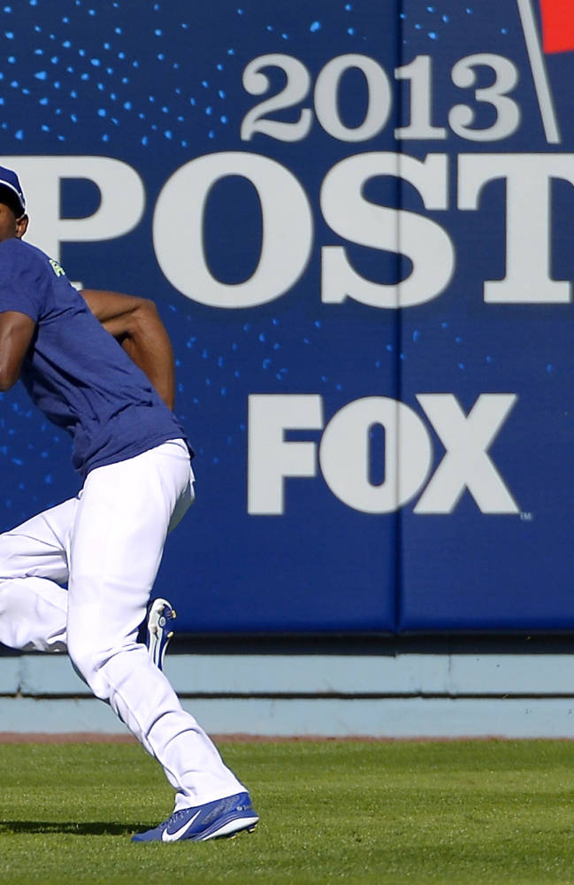 Los Angeles Dodgers' Dee Gordon runs back to make a catch during practice in preparation for Game 3 of the National League baseball division series against the Atlanta Braves, Saturday, Oct. 5, 2013, in Los Angeles