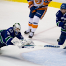 Vancouver Canucks' goalie Eddie Lack, left, of Sweden, dives to make the save as Dan Hamhuis covers the empty net during third period NHL hockey action against the New York Islanders in Vancouver, British Columbia, on Monday March 10, 2014 The Associated