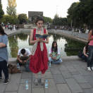 In this photo taken Tuesday, June 18, 2013, a woman stands in a silent protest as others read at Kizilay Square in Ankara, Turkey. After weeks of sometimes-violent confrontation with police, Turkish protesters have found a new form of resistance: standing still and silent. (AP Photo)