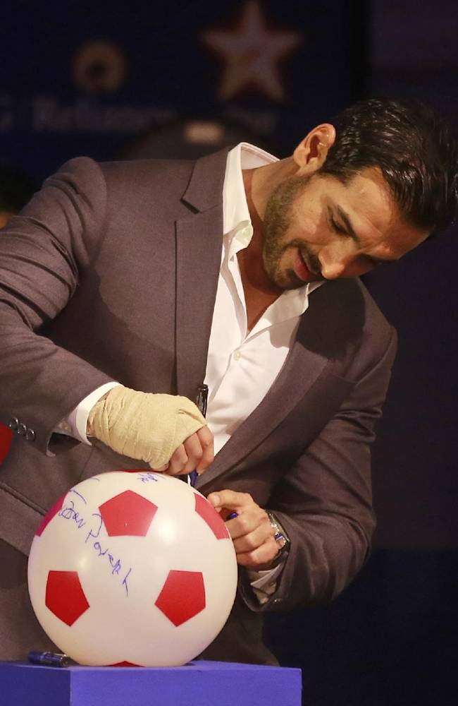 John Abraham, Bollywood actor and co-owner of NorthEast United FC, signs a soccer ball during the official launch of the Indian Super League (ISL) in Mumbai, India, Thursday, Aug. 28, 2014. The ISL, an initiative to popularize soccer in the country, is scheduled to begin Oct. 12
