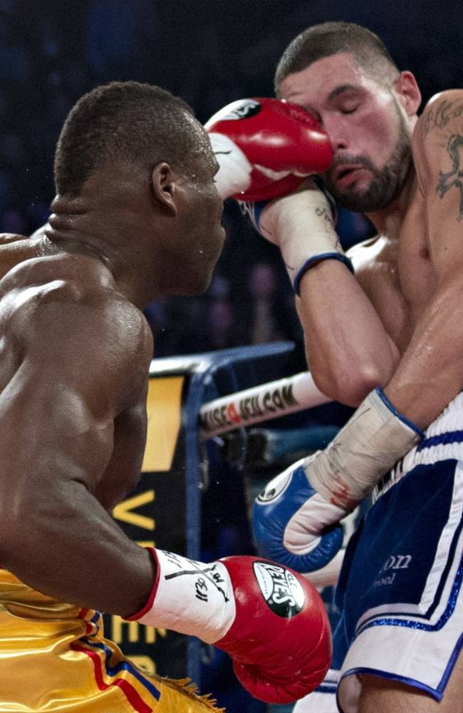 Adonis Stevenson, left, of Canada, lands a left hand to the the face of Tony Bellew, of England, in their WBC light heavyweight title fight in Quebec City early Sunday, Dec. 1, 2013. Stevenson won the fight