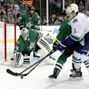 Dallas Stars goalie Kari Lehtonen (32), of Finland, watches the puck as Ryan Garbutt helps against pressure at the net by Vancouver Canucks' Luca Sbisa (5), of Italy, during the second period of an NHL hockey game, Tuesday, Oct. 21, 2014, in Dallas The As