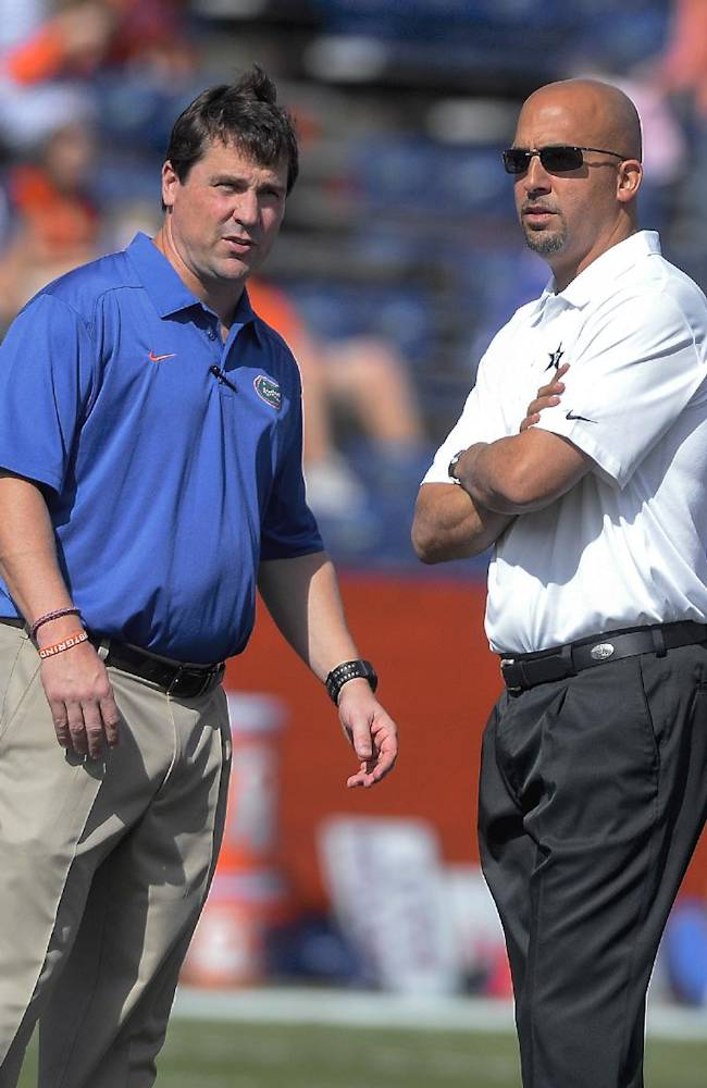 Florida coach Will Muschamp, left and Vanderbilt coach James Franklin, right, watch their teams warmup as the two met together before during the first half of an NCAA college football game Saturday, Nov. 9, 2013 in Gainesville, Fla