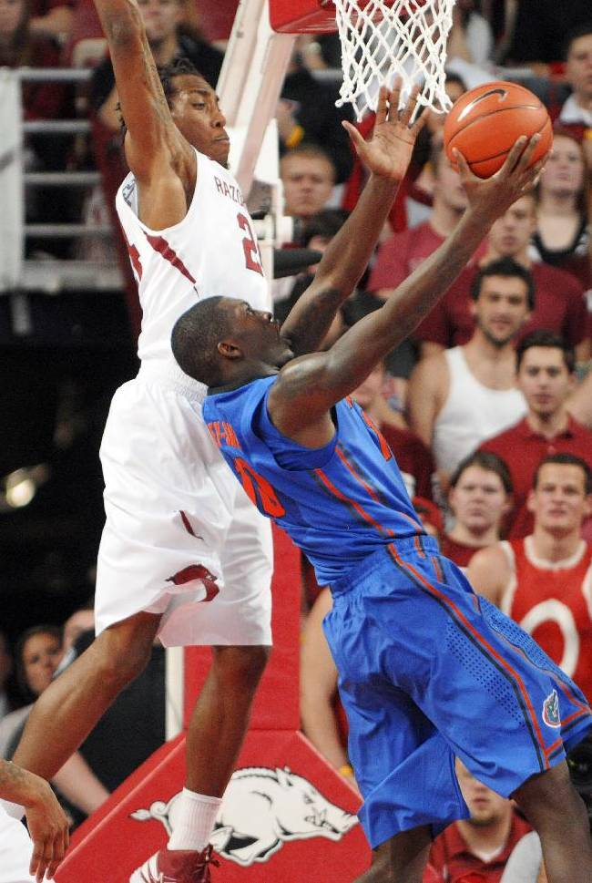 Flolrida forward Dorian Finney-Smith, front, makes a reverse layup while being guarded by Arkansas guard Michael Qualls during an NCAA college basketball game in Fayetteville, Ark., Saturday, Jan. 11, 2014. Florida won 84-82