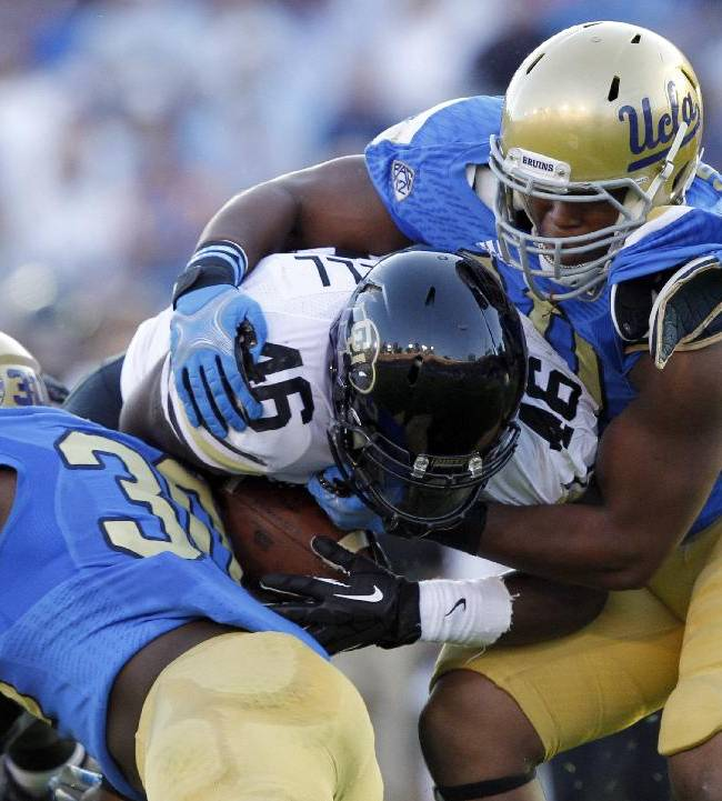 Colorado running back Christian Powell, center, is stopped by UCLA linebacker Myles Jack, left, and UCLA defensive end Keenan Graham, right, for no gain in the first half of their NCAA college football game Saturday, Nov. 2, 2013, in Pasadena, Calif