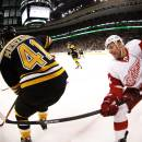 In a photo made with a fish eye lens, Detroit Red Wings' Daniel Alfredsson tries to check Boston Bruins' Andrej Meszaros (41) during the third period of Boston's 4-1 win in Game 2 of a first-round NHL hockey playoff series in Boston Sunday, April 20, 2014. (AP Photo/Winslow Townson)