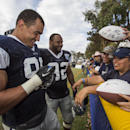 Dallas Cowboys defensive end Tyrone Crawford (98), left, and teammate defensive end Jeremy Mincey (92) sign autographs at the end of practice at NFL football training camp, Wednesday, July 30, 2014, in Oxnard, Calif The Associated Press