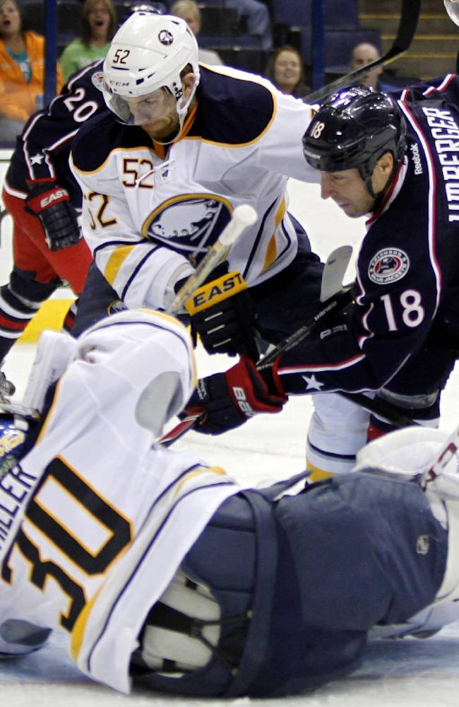 Columbus Blue Jackets' R.J. Umberger (18) scores against Buffalo Sabres goalie Ryan Miller (30) and Alexander Sulzer (52), of Germany, in the second period of a preseason NHL hockey game in Columbus, Ohio, Tuesday, Sept. 17, 2013