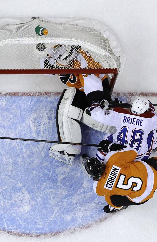 Montreal Canadiens' Daniel Briere, center, collides with Philadelphia Flyers' Steve Mason, top, as Braydon Coburn defends during the third period of an NHL hockey game, Wednesday, Jan. 8, 2014, in Philadelphia. Briere was penalized for goal tender interference on the hit. Philadelphia won 3-1