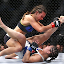 Miesha Tate, left, holds down Jessica Eye during their women's bantamweight mixed martial arts bout during UFC Chicago on Saturday, July 25, 2015, in Chicago. (AP Photo/Jeff Haynes)
