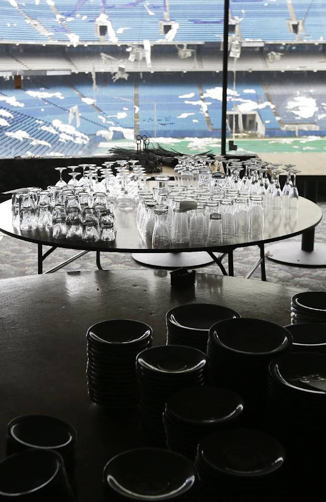 In this May 12, 2014 photo, glassware is setup for auction inside the Pontiac Silverdome in Pontiac, Mich. The venue is a shell of its former self with its roof in tatters and a lack of electrical power that has left the stadium's innards dark and mold-covered. The Silverdome's current owner is determined to cash in before it's too late, putting everything inside up for auction starting on Wednesday, May 21