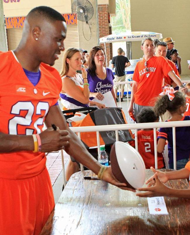Clemson NCAA college football running back D. J. Howard, left, hands an autographed football back to a young fan at the Tigers' Fan Appreciation Day at Memorial Stadium in Clemson, S.C., on Sunday, Aug, 17, 2014