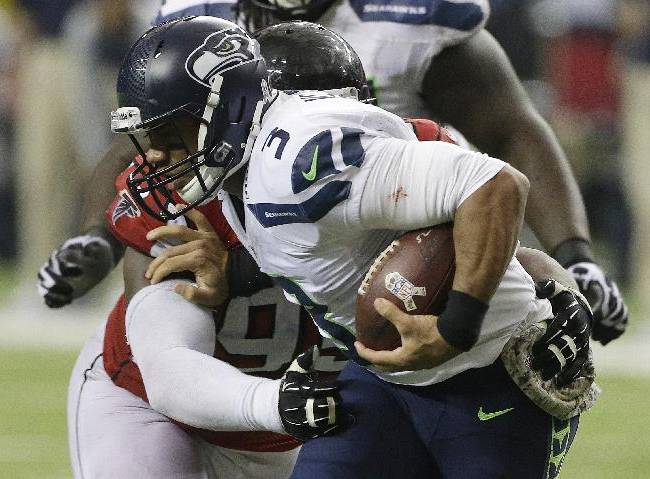 Atlanta Falcons defensive tackle Jonathan Babineaux (95) hits Seattle Seahawks quarterback Russell Wilson (3) during the second half of an NFL football game, Sunday, Nov. 10, 2013, in Atlanta