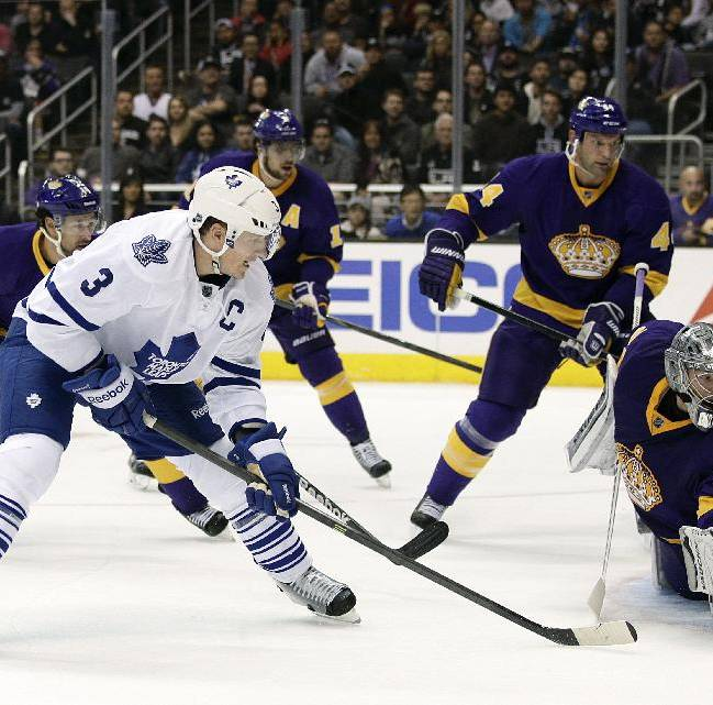 Toronto Maple Leafs' Dion Phaneuf, left, scores against Los Angeles Kings goalie Jonathan Quick during the first period of an NHL hockey game on Thursday, March 13, 2014, in Los Angeles
