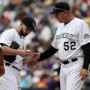 Colorado Rockies starting pitcher Tyler Chatwood, left, confers with pitching coach Jim Wright after Chatwood loaded the bases with no outs against the San Francisco Giants in the fifth inning of a baseball game in Denver on Wednesday, April 23, 2014 The