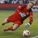 Sporting Kansas City goalkeeper Eric Kronberg dives for the ball during the first half of an MLS soccer match against the Montreal Impact in Kansas City, Kan., Saturday, April 19, 2014. Impact was awarded a corner-kick on the play The Associated Press