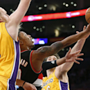 Portland Trail Blazers guard Damian Lillard shoots between Los Angeles Lakers' Chris Kaman, left, and Pau Gasol during the first half of an NBA basketball game in Los Angeles, Tuesday, April 1, 2014 The Associated Press