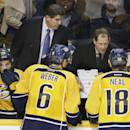 Nashville Predators head coach Peter Laviolette, top left, and assistant coach Phil Housley, top right, talk with players during a timeout against the Los Angeles Kings in overtime at an NHL hockey game Tuesday, Nov. 25, 2014, in Nashville, Tenn. The Predators won 4-3 in a shootout. (AP Photo/Mark Humphrey)