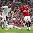 Manchester United's Juan Mata, right, prepares to shoot as Queens Park Rangers' Sandro, top left, and Mauricio Isla collide during their English Premier League soccer match at Old Trafford Stadium, Manchester, England, Sunday Sept. 14, 2014
