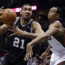 San Antonio Spurs' Tim Duncan is fouled as he drives past Milwaukee Bucks' John Henson during the second half of an NBA basketball game Wednesday, Dec. 11, 2013, in Milwaukee. (AP Photo/Morry Gash)