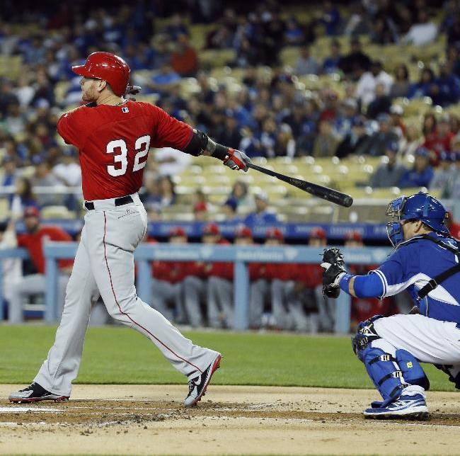Los Angeles Angels' Josh Hamilton watches his three-run home run in front of Los Angeles Dodgers catcher A.J. Ellis during the first inning of an exhibition baseball game in Los Angeles, Friday, March 28, 2014