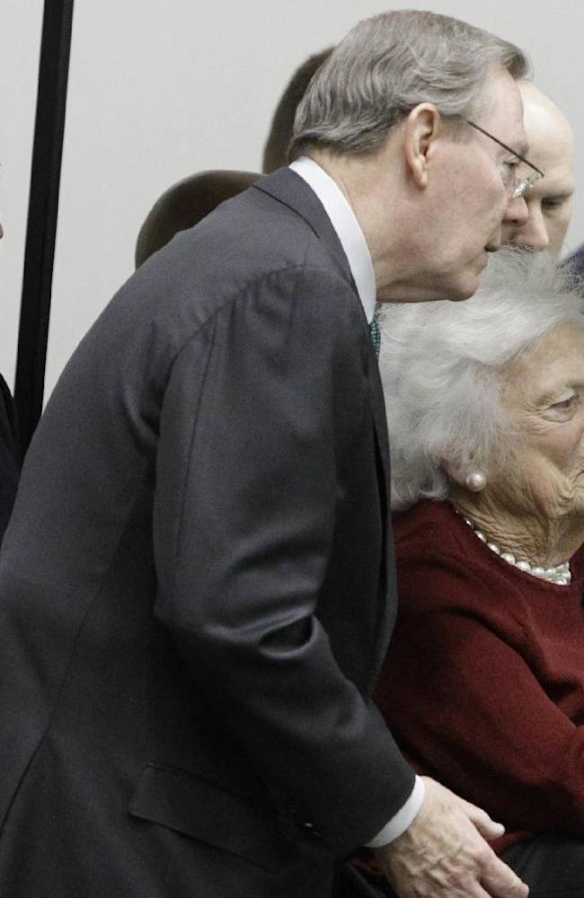 Former President George H.W. Bush, left,  and Barbara Bush, right foreground, attend Texas A&M pro day for NFL football representativesin College Station, Texas, Thursday, March 27, 2014