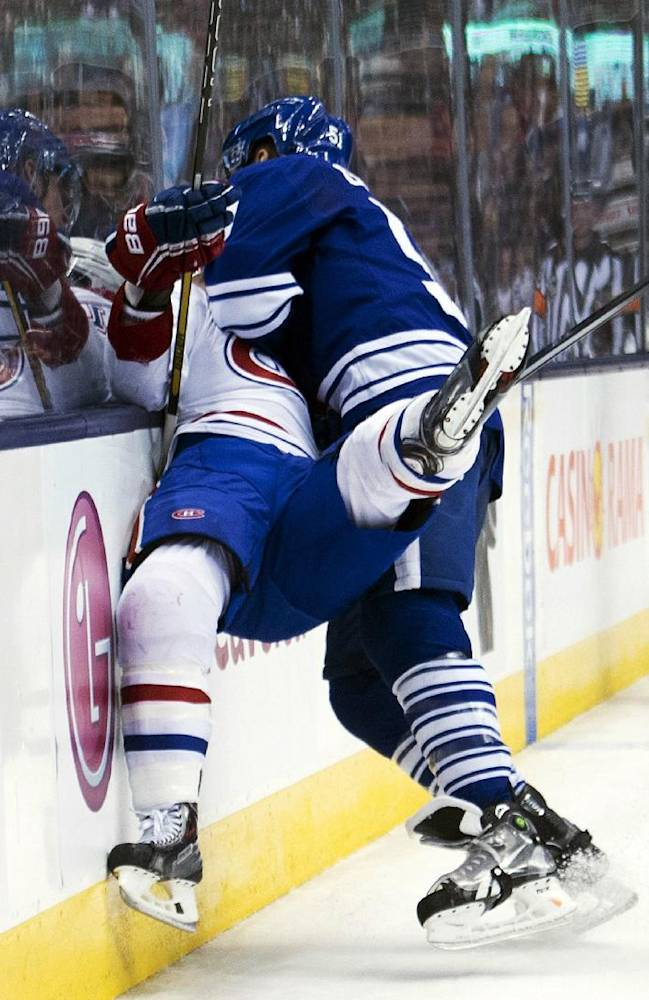 Toronto Maple Leafs defenseman Jake Gardiner, right, takes out Montreal Canadiens forward Brendan Gallagher, left, during the third period of an NHL hockey game in Toronto on Saturday, March 22, 2014